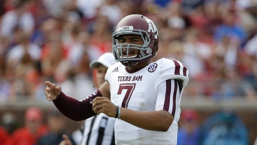 Texas A&M quarterback Kenny Hill (7) instructs his team at the line of scrimmage in the first half of an NCAA college football game against SMU,  Saturday, Sept. 20, 2014, in Dallas. (AP Photo/Tony Gutierrez)