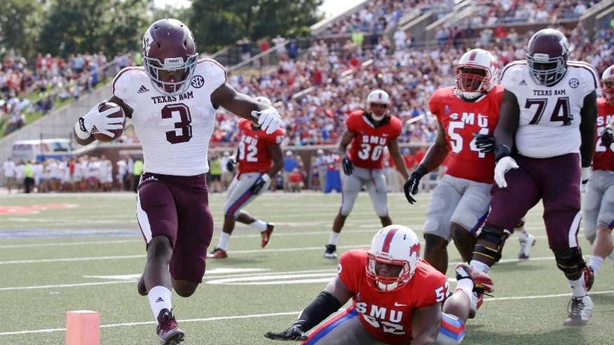 Texas A&M running back Trey Williams (3) high steps into the end zone past SMU linebacker Cameron Nwosu (52) as the Aggies' Germain Ifedi (74) watches in the first half of an NCAA college football game, Saturday, Sept. 20, 2014, in Dallas. (AP Photo/Tony Gutierrez)