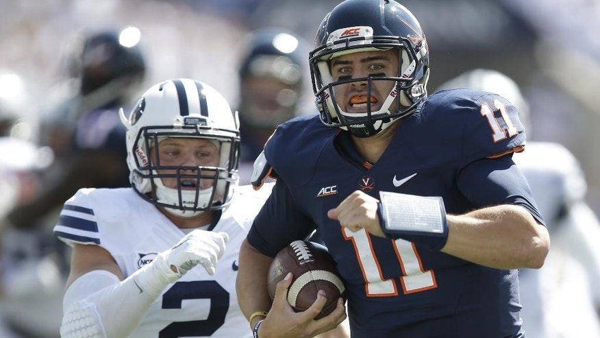 Virginia quarterback Greyson Lambert (11) carries the ball as he is pursued by Brigham Young defensive back Dallin Leavitt (2)in the first quarter during an NCAA college football game Saturday, Sept. 20, 2014, in Provo, Utah. (AP Photo/Rick Bowmer)