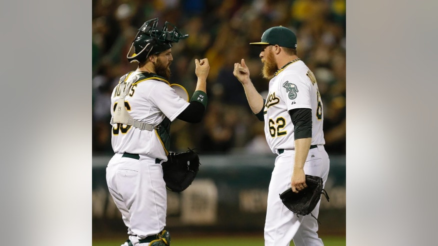 Oakland Athletics' Sean Doolittle (62) and Derek Norris, left, celebrate the A's 3-1 defeat of the Philadelphia Phillies in a baseball game Friday, Sept. 19, 2014, in Oakland, Calif. (AP Photo/Ben Margot)