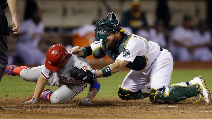 Oakland Athletics catcher Derek Norris, right, tags out Philadelphia Phillies' Freddy Galvis during the eighth inning of a baseball game Friday, Sept. 19, 2014, in Oakland, Calif. Galvis was attempting to score on a ball hit by Carlos Ruiz. (AP Photo/Ben Margot)