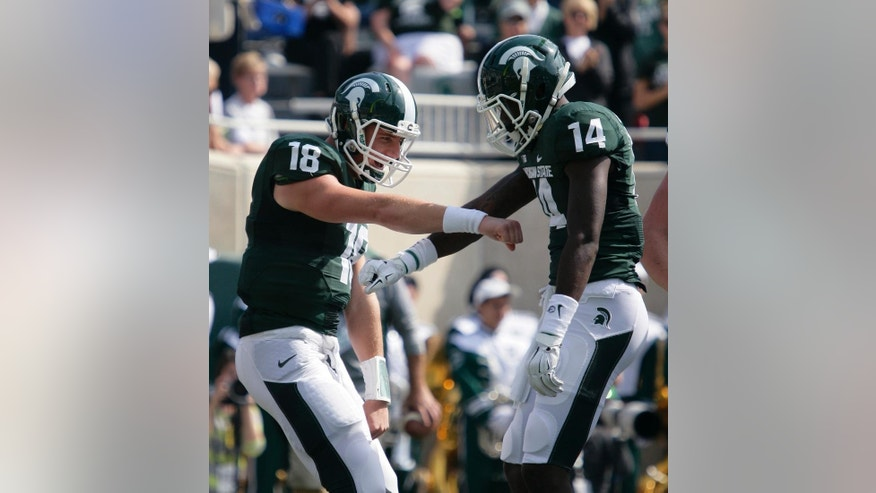 Michigan State quarterback Connor Cook (18) and receiver Tony Lippett (14) celebrate Lippett's touchdown reception against Eastern Michigan during the first quarter of an NCAA college football game, Saturday, Sept. 20, 2014, in East Lansing, Mich. (AP Photo/Al Goldis)