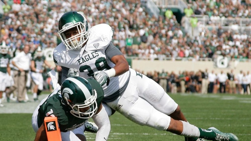 Michigan State receiver A.J. Troup, left, dives for a touchdown against Eastern Michigan's Jason Beck during the second quarter of an NCAA college football game, Saturday, Sept. 20, 2014, in East Lansing, Mich. (AP Photo/Al Goldis)