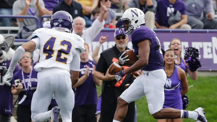 Northwestern running back Solomon Vault (15), right, scores a touchdown against Western Illinois defensive back Myles Spearman (42) during the first half of an NCAA college football game in Evanston, Ill., Saturday, Sept. 20, 2014. (AP Photo/Nam Y. Huh)