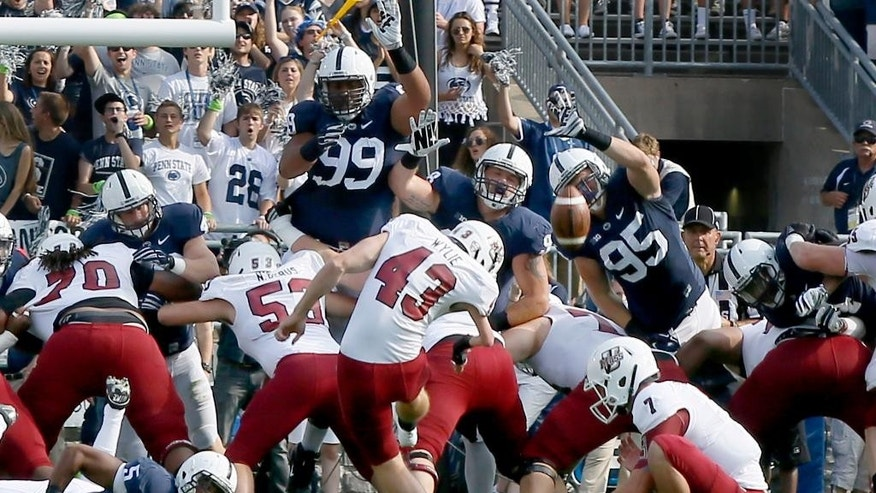 Massachusetts place kicker Matthew Wylie (43) misses a field goal as the Penn State defensive end Carl Nassib (95) leaps with the rest of the line in the first quarter of the  NCAA football game on Saturday, Sept. 20, 2014, in State College, Pa. (AP Photo/Keith Srakocic)