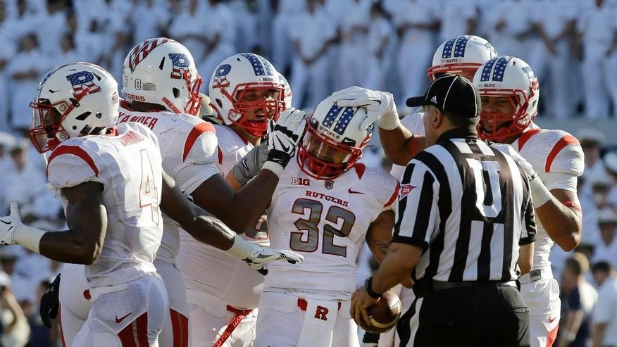 Rutgers running back Justin Goodwin (32) celebrates his touchdown with teammates in the first half of an NCAA college football game against Navy in Annapolis, Md., Saturday, Sept. 20, 2014. (AP Photo/Patrick Semansky)