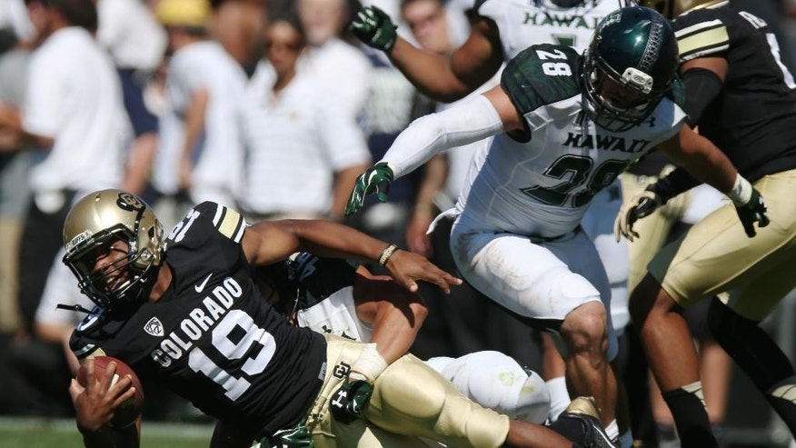 Colorado tailback Michael Adkins II, left, is pulled down after a short gain by Hawaii defensive back Michael Martin, front right, as linebacker Julian Gener, back right, covers in the third quarter of an NCAA college football game in Boulder, Colo., on Saturday, Sept. 20, 2014. (AP Photo/David Zalubowski)