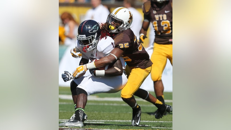 Florida Atlantic's Lucky Whitehead is tackled by Wyoming defender Robert Priester during the first half of an NCAA college football game Saturday, Sept. 20, 2014, in Laramie, Wyo. (AP Photo/The Wyoming Tribune Eagle, Michael Smith)