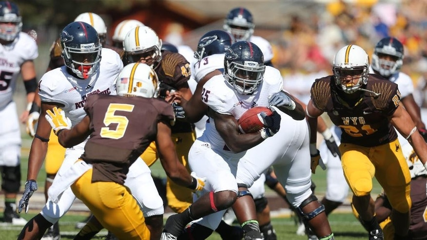 Florida Atlantic running back Jay Warren runs through Wyoming defenders during the first half of an NCAA college football game Saturday, Sept. 20, 2014, in Laramie, Wyo. (AP Photo/The Wyoming Tribune Eagle, Michael Smith)
