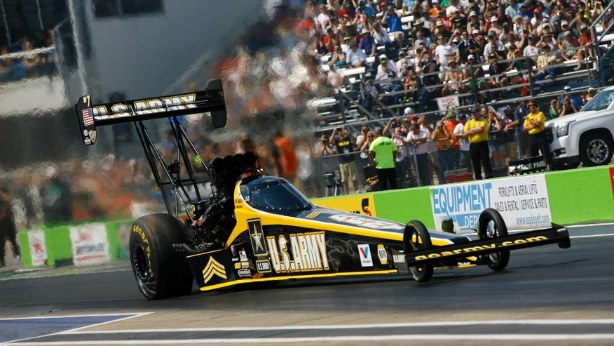 In this photo provided by NHRA, Tony Schumacher drives to victory in Top Fuel at the delayed Pep Boys NHRA Carolina Nationals on Saturday, Sept. 20, 2014, at Texas Motorplex in Ennis, Texas. Schumacher earned his 75th career victory when he defeated Khalid alBalooshi in the final round of the race that was originally started one week ago at zMAX Dragway in Charlotte, N.C. (AP Photo/NHRA, Randy Anderson)