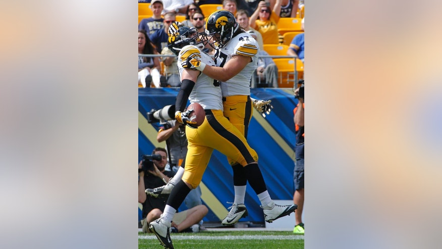 Iowa tight end Henry Krieger Coble, left, celebrates with Iowa linebacker John Kenny (47) after catching a pass in the endzone for a first-quarter touchdown during an NCAA college football game against Pittsburgh in Pittsburgh Saturday, Sept. 20, 2014. (AP Photo/Gene Puskar)