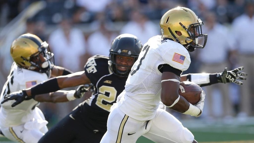 Army quarterback Angel Santiago, right, runs past Wake Forest safety Josh Okonye, back, during the first half of an NCAA college football game in Winston-Salem, N.C., Saturday, Sept. 20, 2014. (AP Photo/Chuck Burton)
