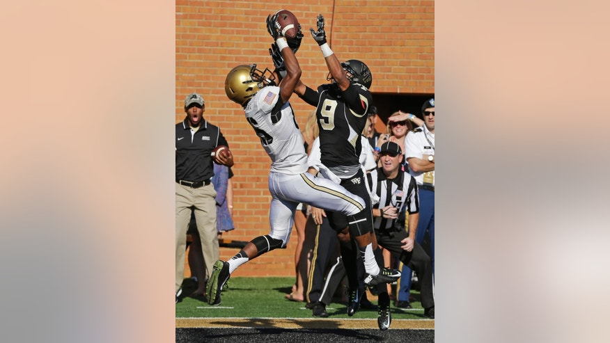 Army wide receiver Xavier Moss, left, catches a touchdown pass as Wake Forest cornerback Kevin Johnson, right, defends during the first half of an NCAA college football game in Winston-Salem, N.C., Saturday, Sept. 20, 2014. (AP Photo/Chuck Burton)