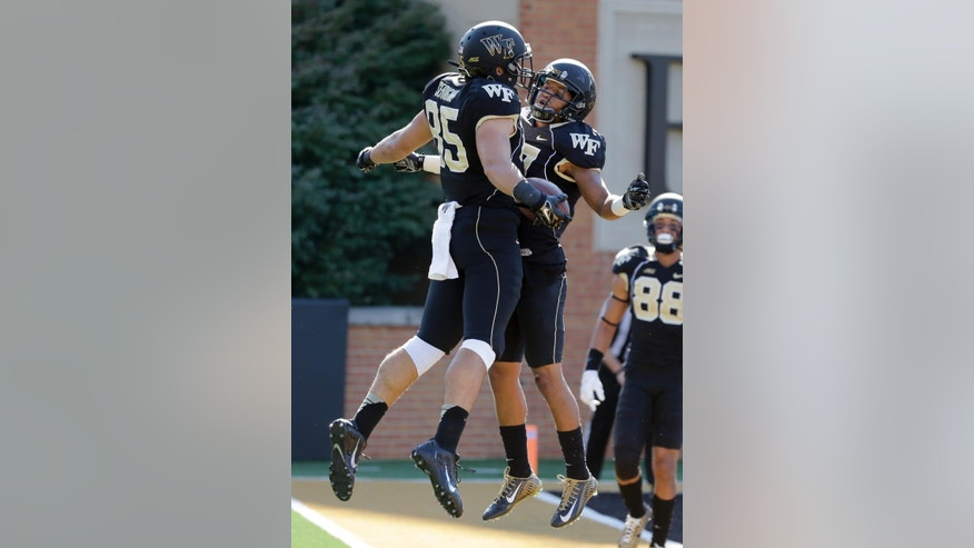 Wake Forest tight end Cam Serigne (85) celebrates his touchdown catch against Army with teammate E.J. Scott, right, during the first half of an NCAA college football game in Winston-Salem, N.C., Saturday, Sept. 20, 2014. (AP Photo/Chuck Burton)