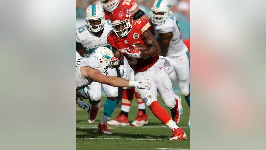 Kansas City Chiefs running back Knile Davis (34) avoids a tack Miami Dolphins outside linebacker Jason Trusnik (93) as he runs to the end zone for a touchdown during the first half of an NFL football game, Sunday, Sept. 21, 2014, in Miami Gardens, Fla. (AP Photo/Wilfredo Lee)