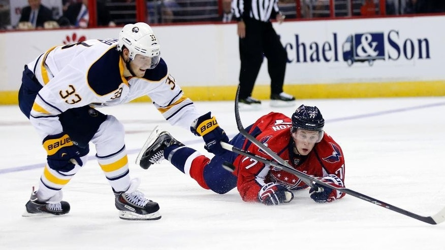 Washington Capitals defenseman Tyler Lewington (77) dives for the puck as Buffalo Sabres right wing Joel Armia (33), from Finland, reaches in the second period of a preseason NHL hockey game, Sunday, Sept. 21, 2014, in Washington. (AP Photo/Alex Brandon)
