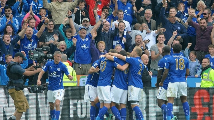 Leicester City players celebrates after Leonardo Ulloa, hidden, scored a penalty to beat Manchetser United 5-3 during the English Premier League soccer match between Leicester City and Manchester United at King Power Stadium, in Leicester, England, Sunday, Sept. 21, 2014.  (AP Photo/Rui Vieira)