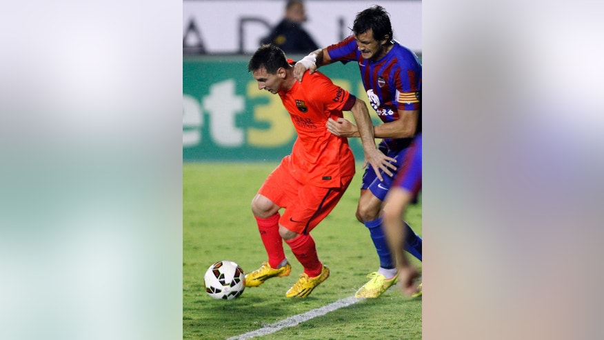 Barcelona's Lionel Messi, from Argentina, left, duels for the ball with Levante's  Hector Rodas during a Spanish La Liga soccer match at the Ciutat de Valencia stadium in Valencia, Spain, on Sunday, Sept. 21, 2014.(AP Photo/Alberto Saiz)