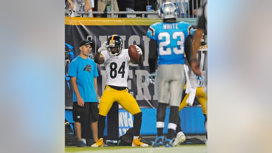 Pittsburgh Steelers' Antonio Brown (84) celebrates his touchdown catch as Carolina Panthers' Melvin White (23) watches on during the second half of an NFL football game in Charlotte, N.C., Sunday, Sept. 21, 2014. (AP Photo/Mike McCarn)