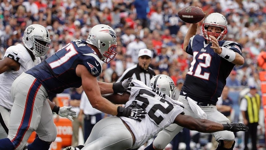 Oakland Raiders outside linebacker Khalil Mack (52) pressures New England Patriots quarterback Tom Brady (12) in the first half of an NFL football game Sunday, Sept. 21, 2014, in Foxborough, Mass. (AP Photo/Steven Senne)