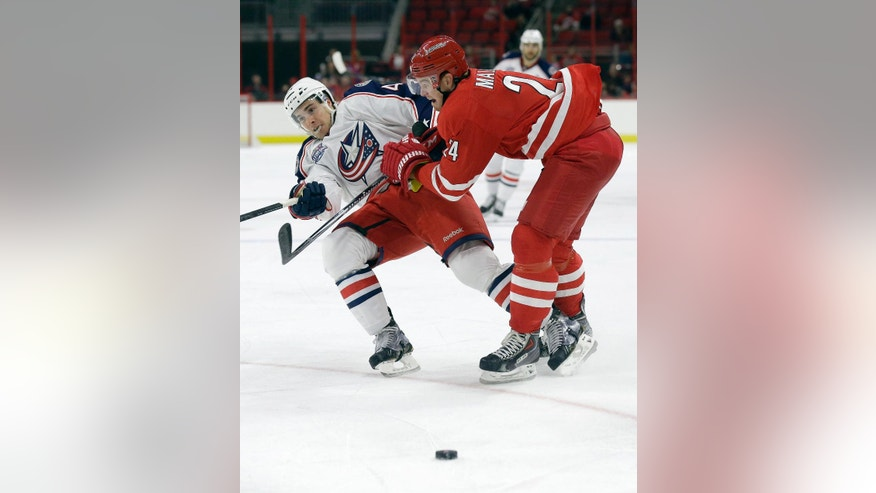 Carolina Hurricanes' Brad Malone (24) hits Columbus Blue Jackets' Will Weber (44) during the first period of an NHL preseason hockey game in Raleigh, N.C., Sunday, Sept. 21, 2014. (AP Photo/Gerry Broome)