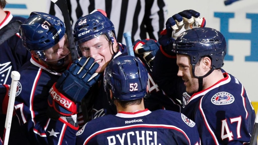 Columbus Blue Jackets' Dillon Heatherington (64) is congratulated by teammates Nick Moutrey (67), Kerby Rychel (52) and Dalton Prout (47) after his goal against the St. Louis Blues in overtime period of an NHL preseason hockey game in Columbus, Ohio, Sunday, Sept. 21, 2014. The Blue Jackets won 4-3. (AP Photo/Paul Vernon)