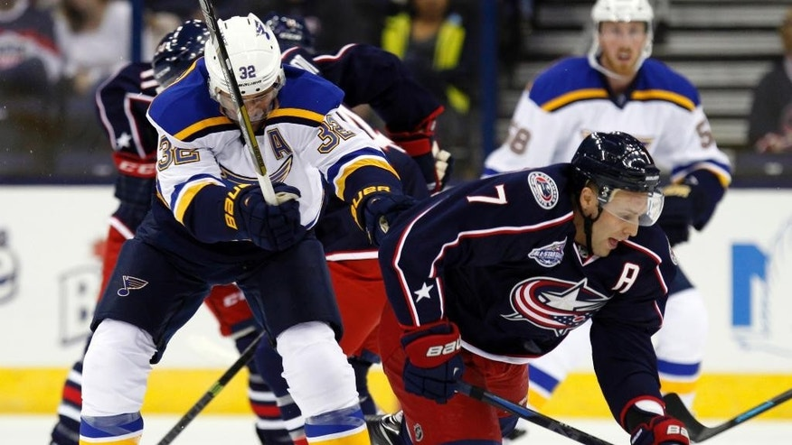 St. Louis Blues' Chris Porter, left, checks Columbus Blue Jackets' Jack Johnson in the first period of an NHL preseason hockey game in Columbus, Ohio, Sunday, Sept. 21, 2014. (AP Photo/Paul Vernon)
