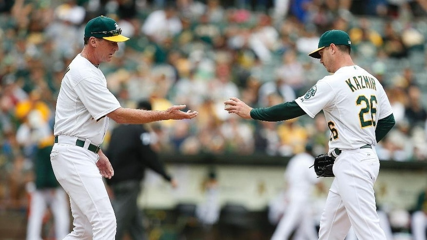 Oakland Athletics pitcher Scott Kazmir, right, is taken out of the baseball game by manager Bob Melvin, left, during the sixth against the Philadelphia Phillies on Sunday, Sept. 21, 2014, in Oakland, Calif. (AP Photo/Tony Avelar)