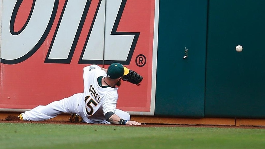 Oakland Athletics left fielder Jonny Gomes can't make the catch on a hit by Philadelphia Phillies' Ben Revere in the sixth inning of a baseball game Sunday, Sept. 21, 2014, in Oakland, Calif. (AP Photo/Tony Avelar)