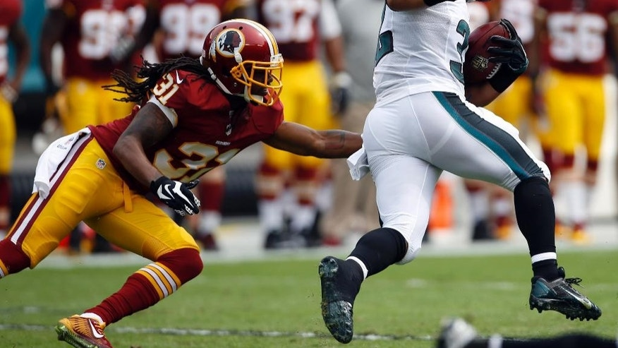 Philadelphia Eagles running back Chris Polk, right, avoids the tackle-attempt of Washington Redskins' Brandon Meriweather on a kickoff-return for a score during the first half of an NFL football game, Sunday, Sept. 21, 2014, in Philadelphia. (AP Photo/Michael Perez)