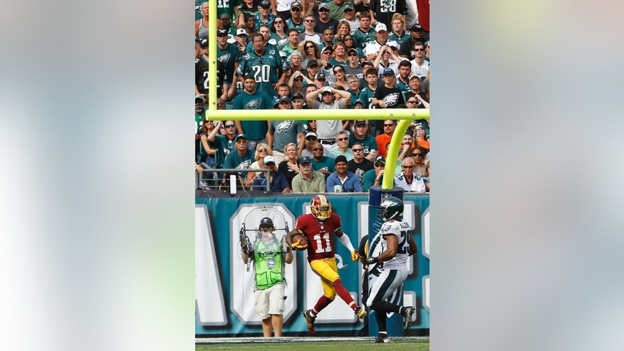 Washington Redskins wide receiver DeSean Jackson (11) looks back while scoring a touchdown as Philadelphia Eagles strong safety Nate Allen chases him during the second half of an NFL football game, Sunday, Sept. 21, 2014, in Philadelphia. (AP Photo/Michael Perez)