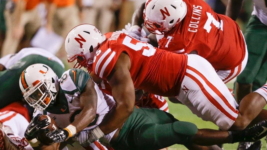 Miami running back Duke Johnson (8) is brought down by Nebraska defensive tackles Kevin Maurice (55) and Maliek Collins (7) in the second half of an NCAA college football game in Lincoln, Neb., Saturday, Sept. 20, 2014. Nebraska won 41-31. (AP Photo/Nati Harnik)
