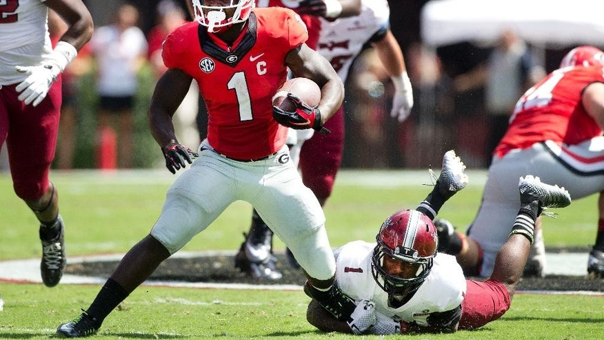 Georgia running back Sony Michel (1) tries to escape from Troy defensive back Montres Kitchens (1) in the first half of an NCAA college football game, Saturday, Sept. 20, 2014, in Athens, Ga. Georgia won 66-0. (AP Photo/John Bazemore)