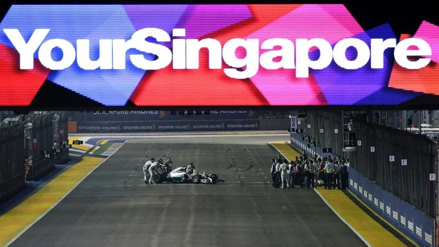 Mechanics push the car of Mercedes driver Nico Rosberg of Germany off the grid after he suffered problems with his car, just before the start of the Singapore Formula One Grand Prix on the Marina Bay City Circuit in Singapore, Sunday, Sept. 21, 2014. (AP Photo/Wong Maye-E)