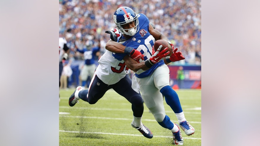 New York Giants wide receiver Victor Cruz (80) is pulled down by Houston Texans cornerback A.J. Bouye (34) on his way to a touchdown in the second quarter of an NFL football game, Sunday, Sept. 21, 2014, in East Rutherford, N.J. (AP Photo/Kathy Willens)