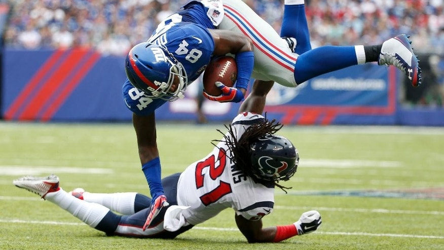 New York Giants tight end Larry Donnell (84) is tripped up by Houston Texans free safety Kendrick Lewis (21) in the second quarter of an NFL football game, Sunday, Sept. 21, 2014, in East Rutherford, N.J. (AP Photo/Kathy Willens)