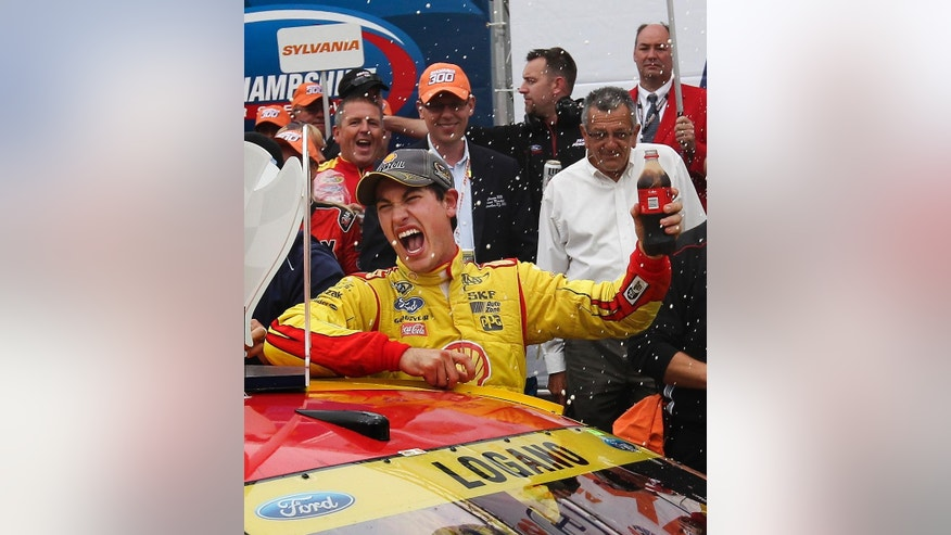Joey Logano celebrates in Victory Lane after winning the NASCAR Sprint Cup series auto race at New Hampshire Motor Speedway in Loudon, N.H., Sunday, Sept. 21, 2014. (AP Photo/Cheryl Senter)