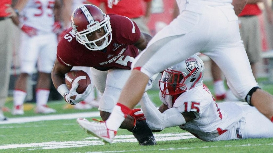 New Mexico State running back Joseph Matthews was brought down by New Mexico's SaQwan Edwards during the first quarter of an NCAA college football game Saturday Sept. 20, 2014 in Las Cruces, N.M. (AP Photo/Victor Calzada)