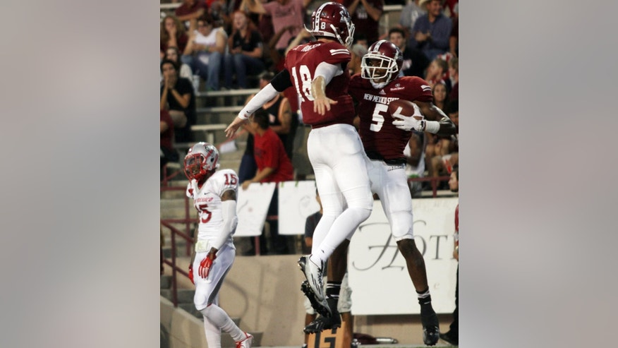 New Mexico State receiver Joseph Matthews, right, celebrates with quarterback Tyler Rogers after they combined for a touchdown pass during the second quarter of an NCAA college football game Saturday Sept. 20, 2014 in Las Cruces, N.M. (AP Photo/Victor Calzada)