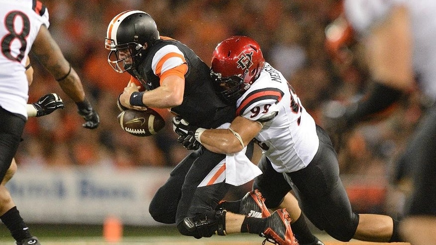 Oregon State quarterback Sean Mannion (4) is sacked by San Diego State defensive end Sam Meredith (98) during the first quarter of an NCAA college football game in Corvallis, Ore., Saturday, Sept. 20, 2014. (AP Photo/Troy Wayrynen)