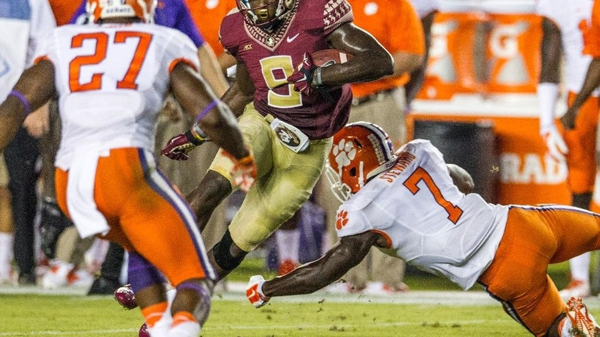 Florida State running back Karlos Williams, center, cuts between Clemson's Robert Smith, left, and Tony Stewart for a 27-yard gain in the first half of an NCAA college football game in Tallahassee, Fla., Saturday, Sept. 20, 2014. (AP Photo/Mark Wallheiser)