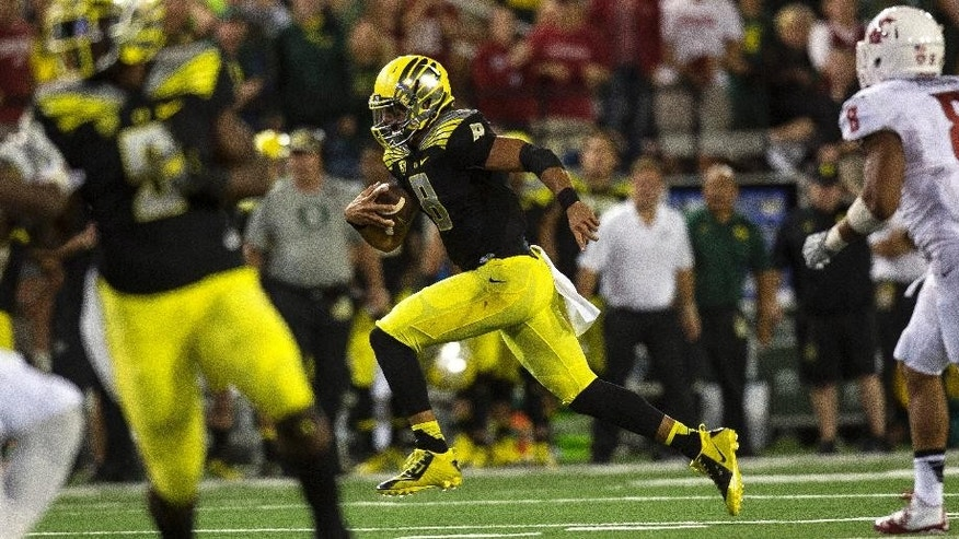 Oregon quarterback Marcus Mariota (8) scrambles for a first down on a 4th down play against Washington State during the third quarter of an NCAA college football game Saturday, Sept. 20, 2014, at Martin Stadium in Pullman, Wash. Oregon won 38-31. (AP Photo/Dean Hare)