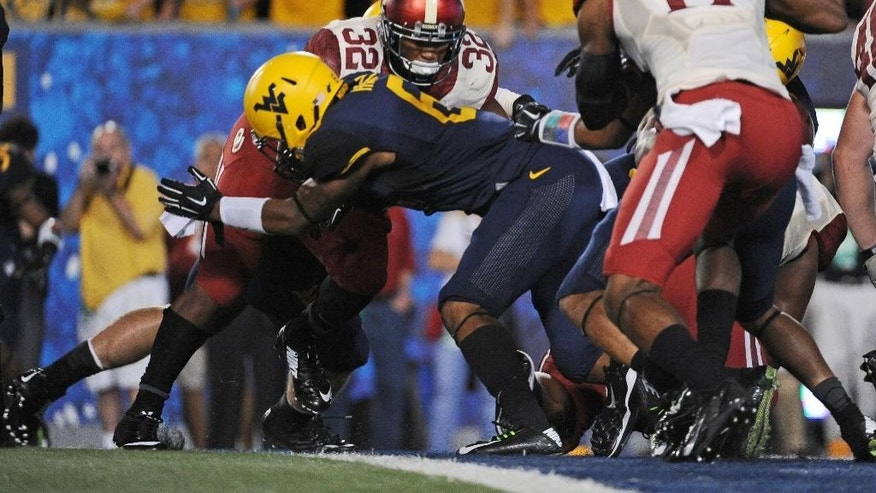 Oklahoma running back Samaje Perine (32) crosses the goal line for a touchdown in the second quarter of an NCAA college football game against West Virginia in Morgantown, W.Va., Saturday, Sept. 20, 2014. (AP Photo/Tyler Evert)