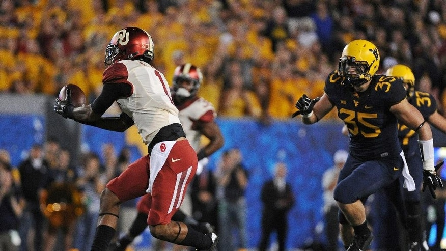 Oklahoma's K.J. Young (1) brings in a pass while West Virginia's Nick Kwiatkoski closes in during the first quarter of an NCAA college football game in Morgantown, W.Va., on Saturday, Sept. 20, 2014. (AP Photo/Tyler Evert)