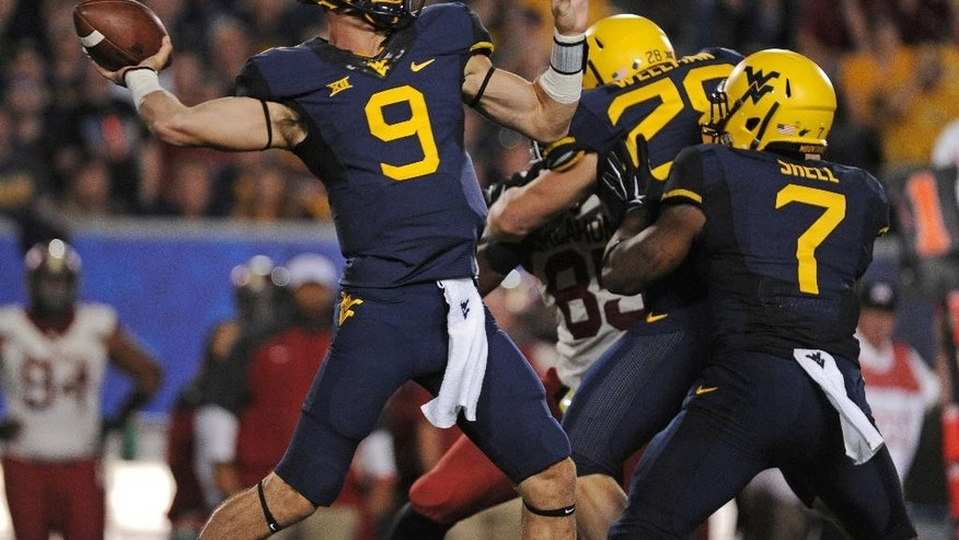 West Virginia quarterback Clint Trickett throws a touchdown pass to receiver Kevin White during the second quarter of an NCAA college football game against Oklahoma in Morgantown, W.Va., Saturday, Sept. 20, 2014. (AP Photo/Tyler Evert)