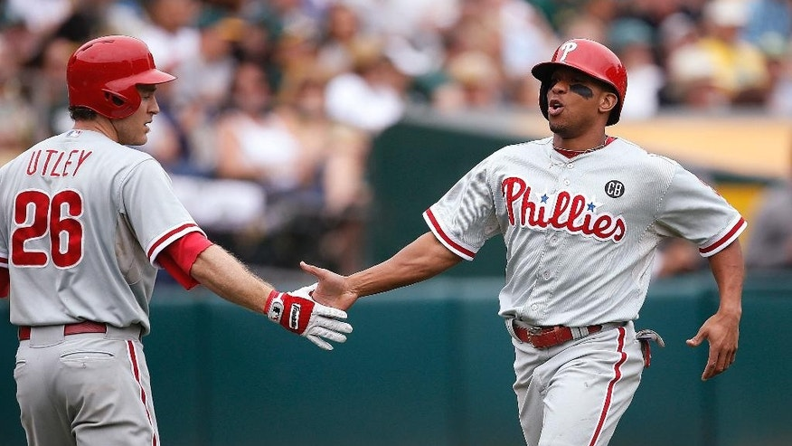 Philadelphia Phillies' Ben Revere, right, is congratulated by Chase Utley after scoring on a hit by Carlos Ruiz against the Oakland Athletics in the fourth inning of a baseball game Sunday, Sept. 21, 2014, in Oakland, Calif. (AP Photo/Tony Avelar)