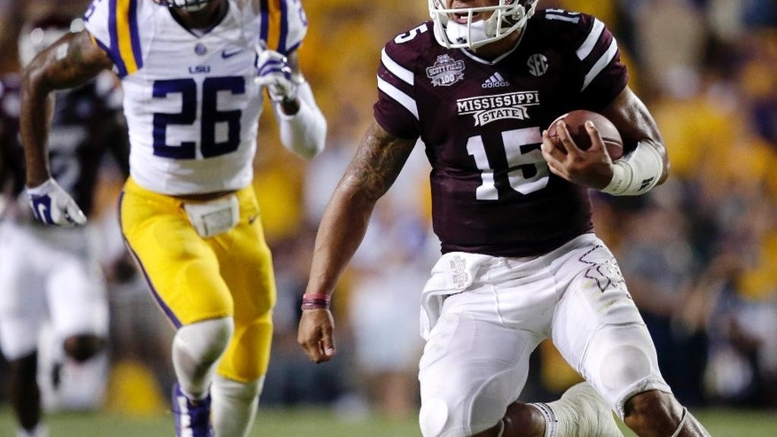 Mississippi State quarterback Dak Prescott (15) carries on a 56 yard touchdown run as he is pursued by LSU safety Ronald Martin (26) in the second half of an NCAA college football game in Baton Rouge, La., Saturday, Sept. 20, 2014. (AP Photo/Gerald Herbert)
