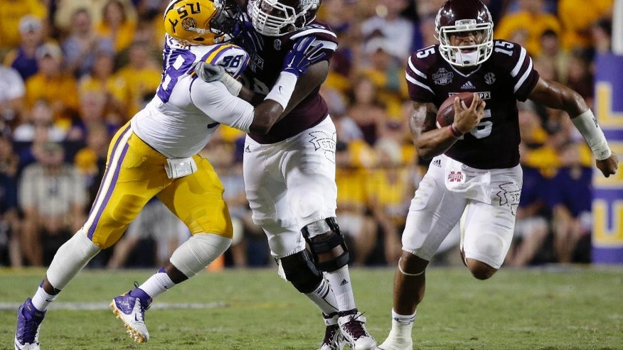 Mississippi State quarterback Dak Prescott (15) carries on a 56 yard touchdown run as offensive linesman Justin Senior blocks out LSU defensive end Deondre Clark (98)  in the second half of an NCAA college football game against Mississippi State in Baton Rouge, La., Saturday, Sept. 20, 2014. (AP Photo/Gerald Herbert)