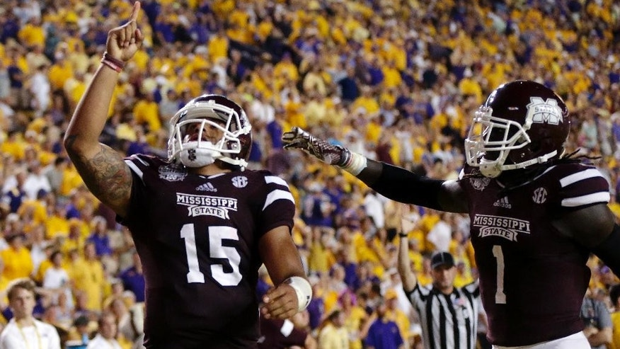 Mississippi State quarterback Dak Prescott (15) celebrates his 56 yard touchdown run with wide receiver De'Runnya Wilson (1) in the second half of an NCAA college football game against Mississippi State in Baton Rouge, La., Saturday, Sept. 20, 2014. (AP Photo/Gerald Herbert)