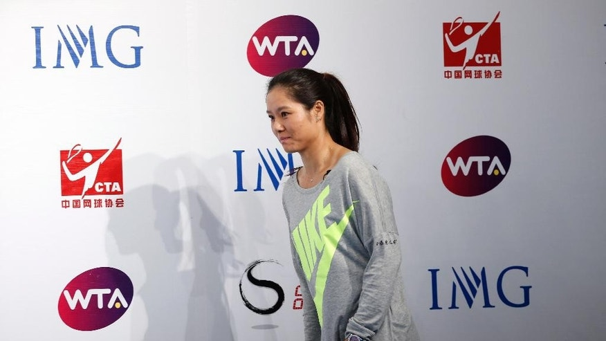 Chinese tennis player Li Na arrives for a press conference to announce her retirement in Beijing, China, Sunday, Sept. 21, 2014. The two-time Grand Slam champion from China who took tennis in Asia to a new level, has retired due to recurring knee injuries. (AP Photo/Vincent Thian)